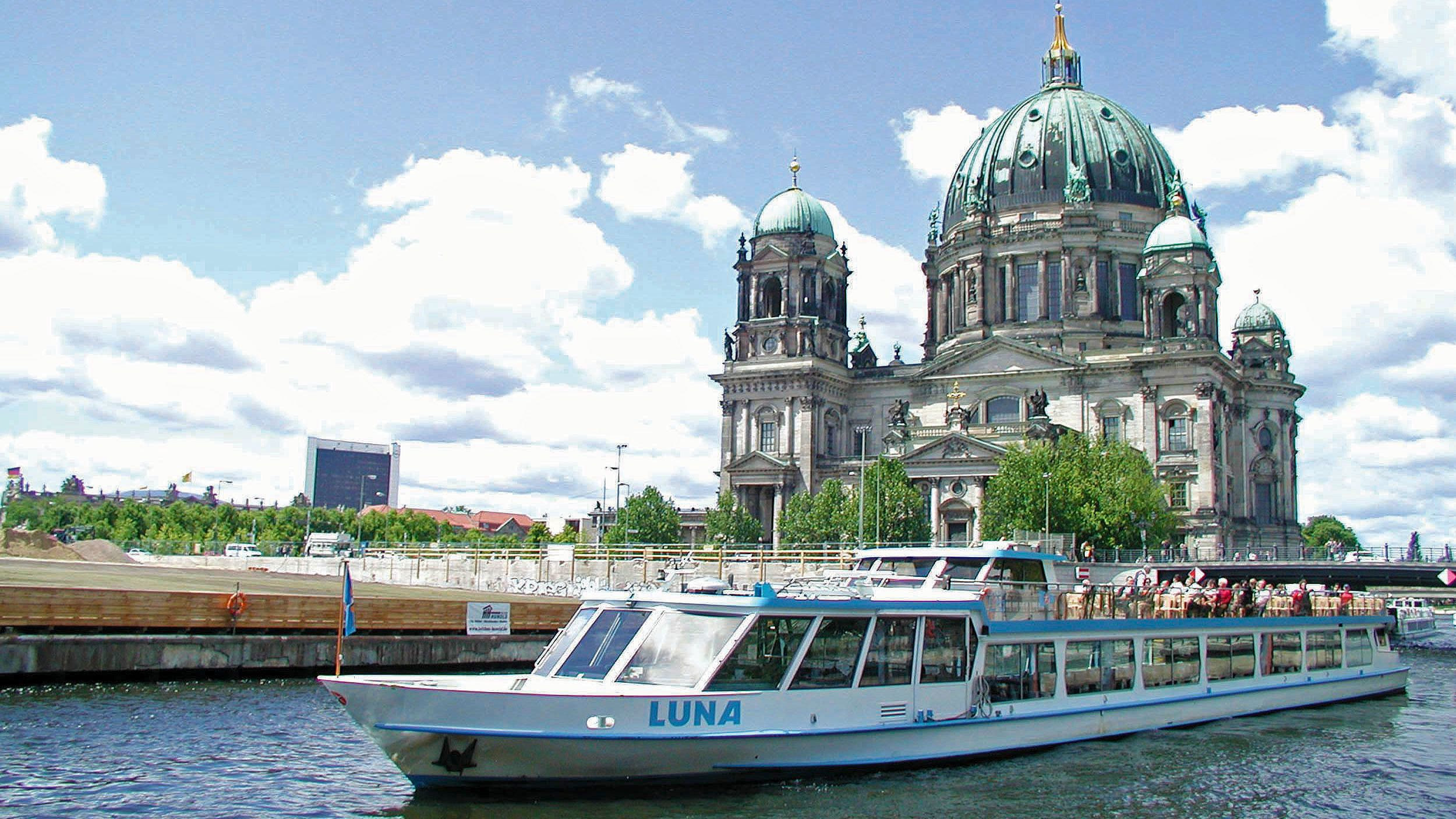 Boat sailing past the Berlin Cathedral on the banks of the Spree river in Berlin