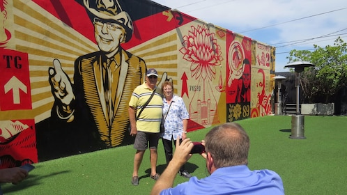Couple posing for a picture in front of a mural on a buildings side