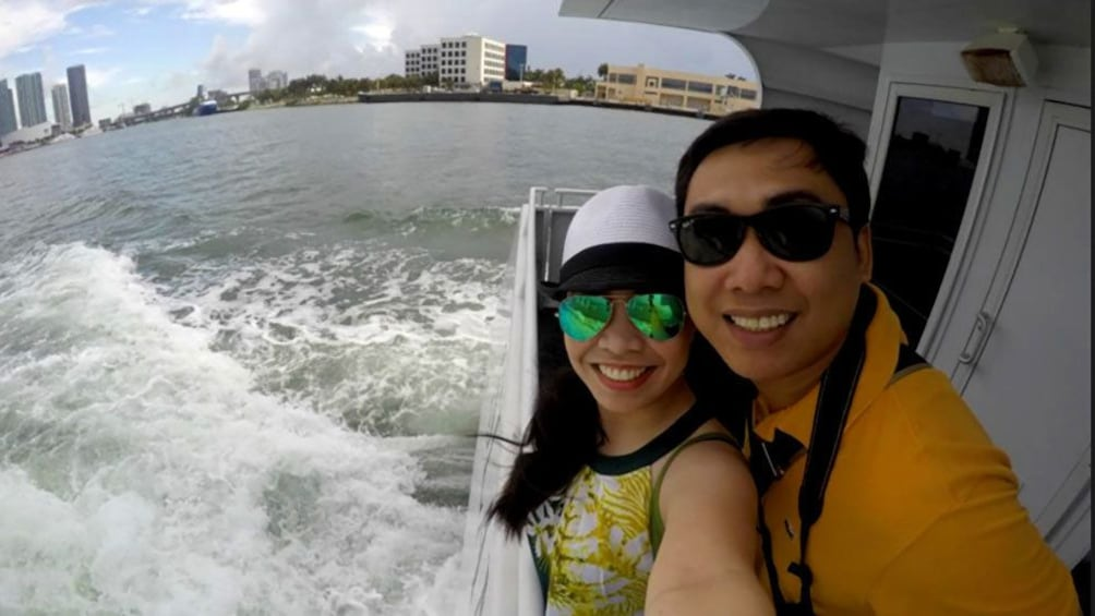 A couple on a boat in Miami taking a selfie