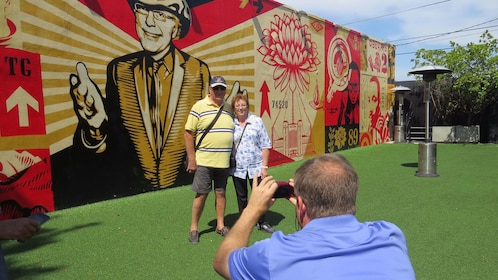 Two people pose for a picture next to a mural