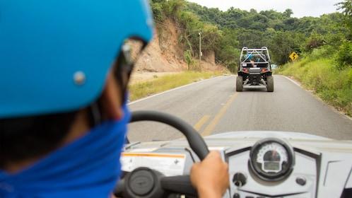 UTV driving man following another UTV on a paved street in Sayulita near Puerto Vallarta.