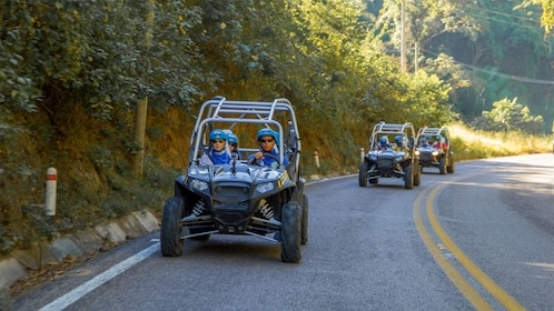 UTV's with group driving down a paved road in Sayulita near Puerto Vallarta.