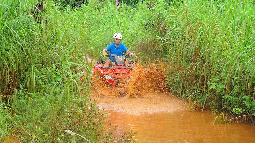 Show item 3 of 8. ATV rider in the mud in guam