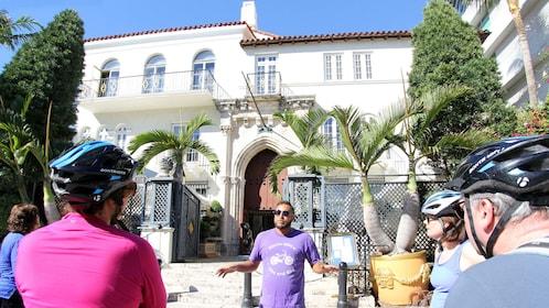 Bike tour guide showcasing mansion in Miami's South Beach