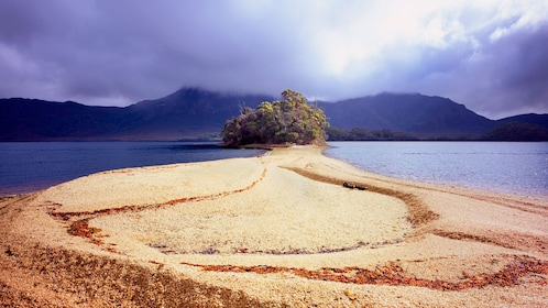 Sandy beach leading to the forest peninsula In Hobart area of Australia.