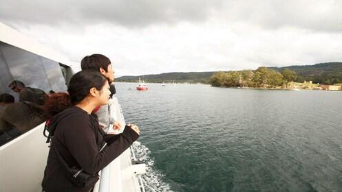 man and woman lean on rail of MV Marana on the harbour cruise at Port Arthur