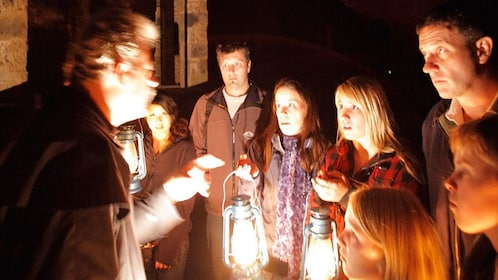 tour guide entertains visitors by oil lamp at Port Arthur in Hobart
