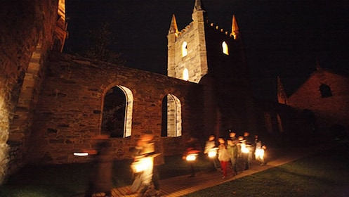 visitors carry oil lamps on path by old stone building at Port Arthur in Hobart
