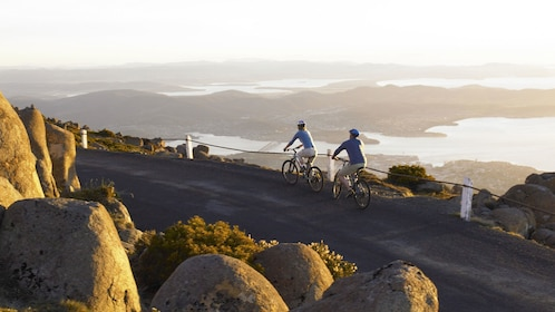 two people on mountain bikes ride on street far above town of Hobart