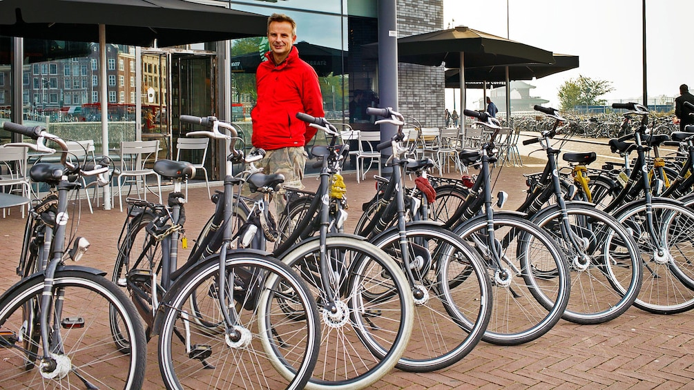 Foto 5 van 9. Man with row of bicycles in Amsterdam
