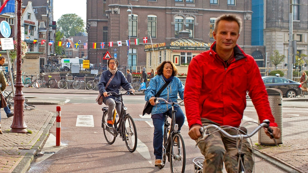 Foto 1 von 9 laden 3 People riding bicycles on brick road in Amsterdam