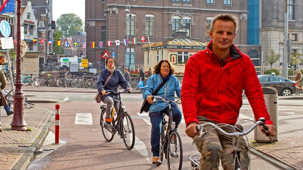 Foto 1 van 9. 3 People riding bicycles on brick road in Amsterdam