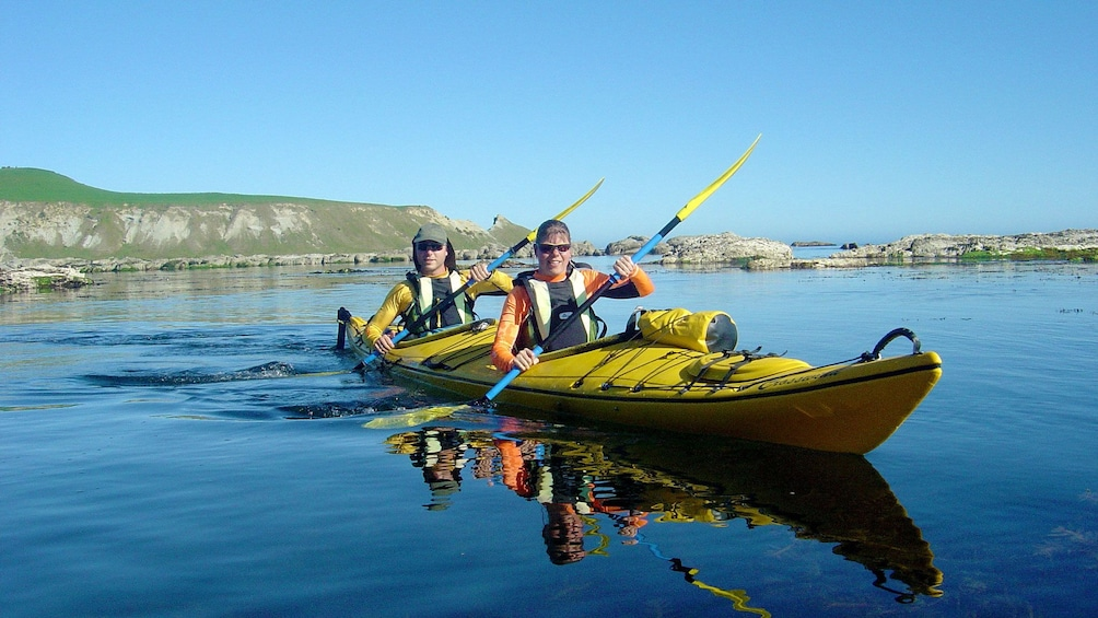 Show item 3 of 5. two men in long kayak paddle together in Taupo