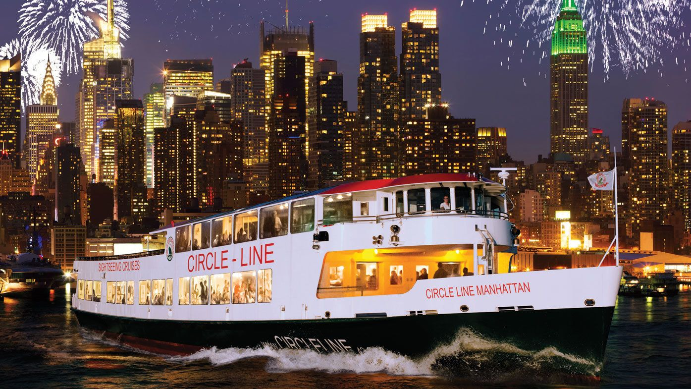 Cruise boat with fireworks and the city at night in New York