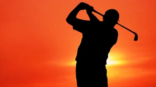 Golfer in full swing at sunset