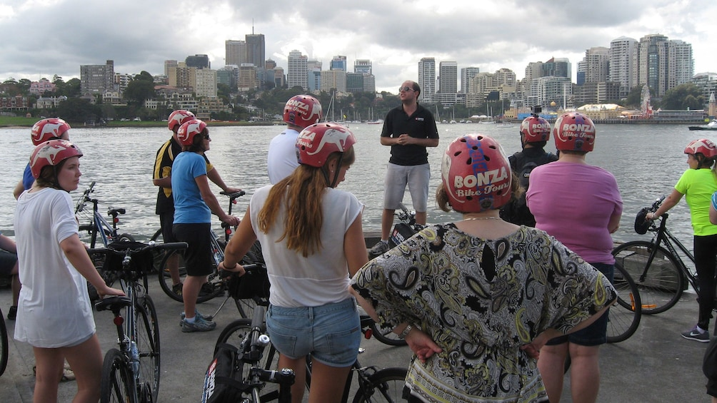 Show item 2 of 9. a group of bicyclists  gather to hear speaker along waterfront in Sydney