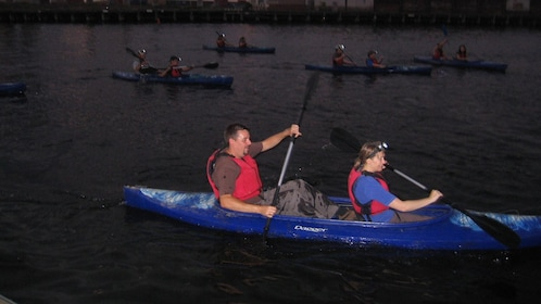 Group of people in canoes in the the Melbourne City Lights Paddle tour in Australia.