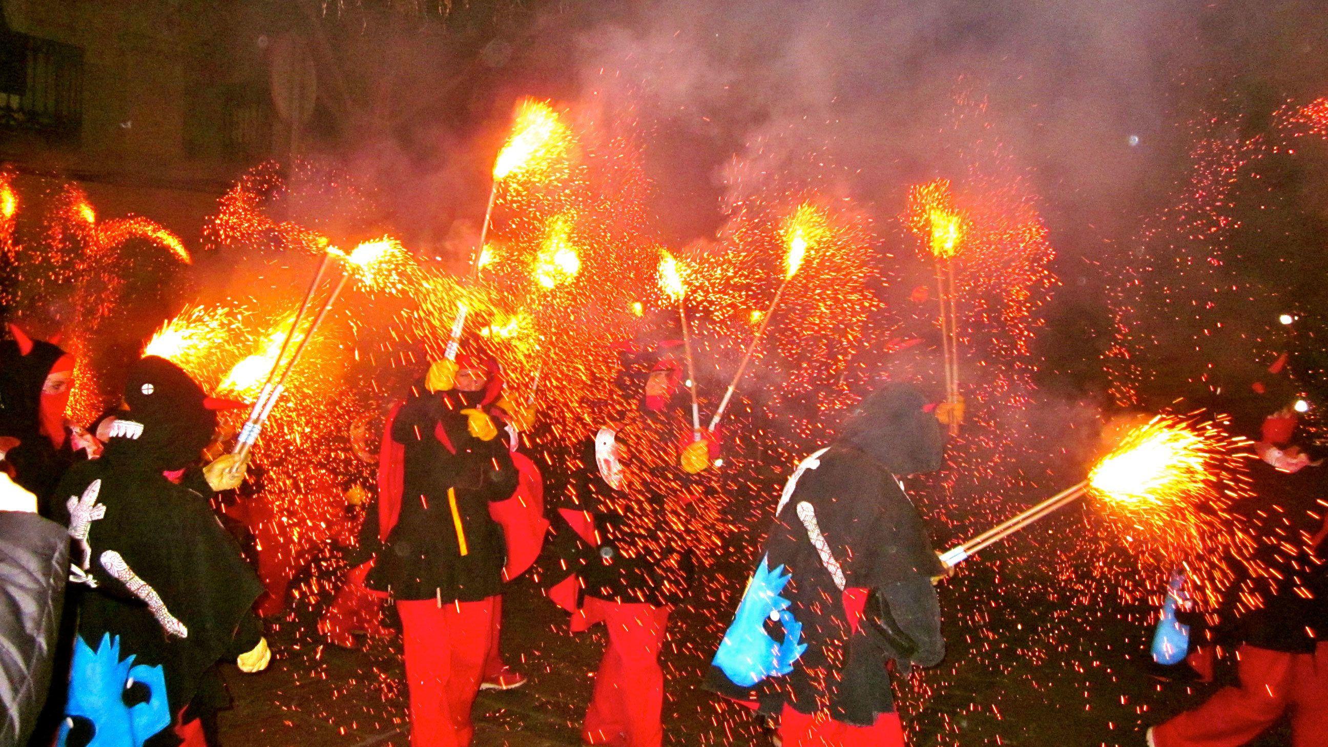 group of people waving fireworks for correfoc celebration in Barcelona