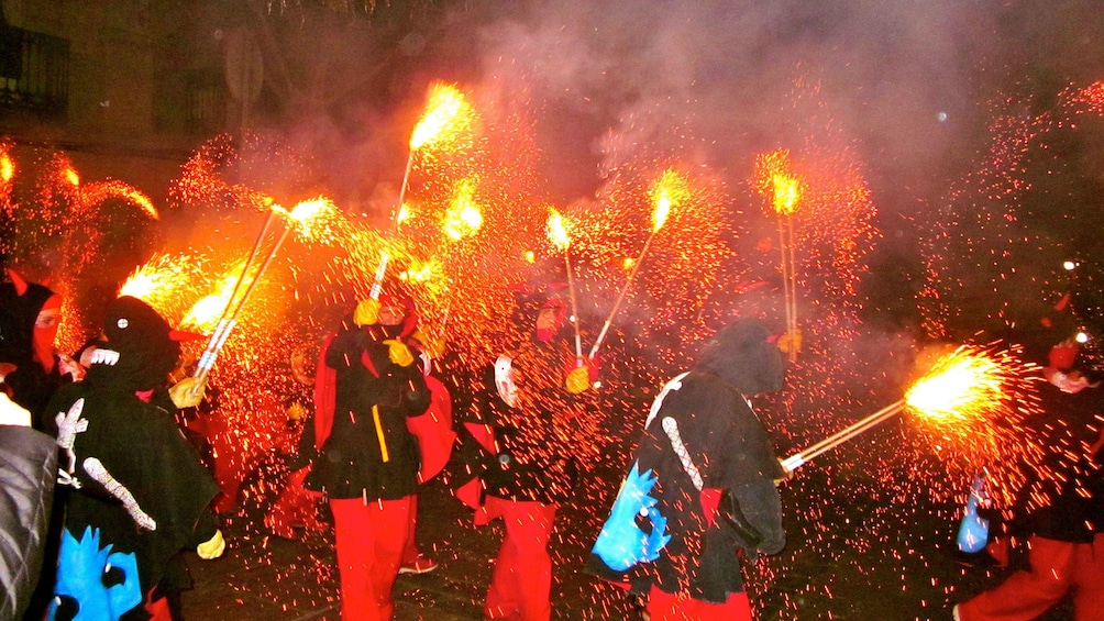 Show item 5 of 5. group of people waving fireworks for correfoc celebration in Barcelona
