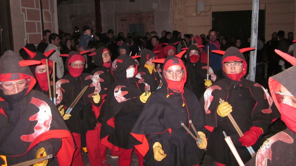 Show item 2 of 5. group of people dressed in costume for correfoc celebration in Barcelona