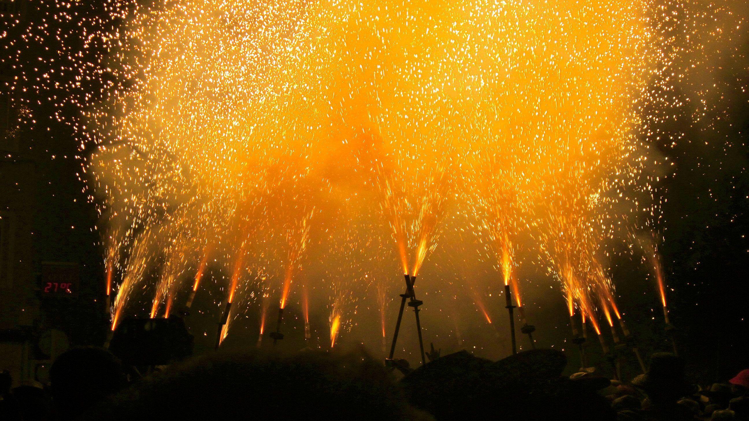 group of people lighting fireworks for correfoc celebration in Barcelona