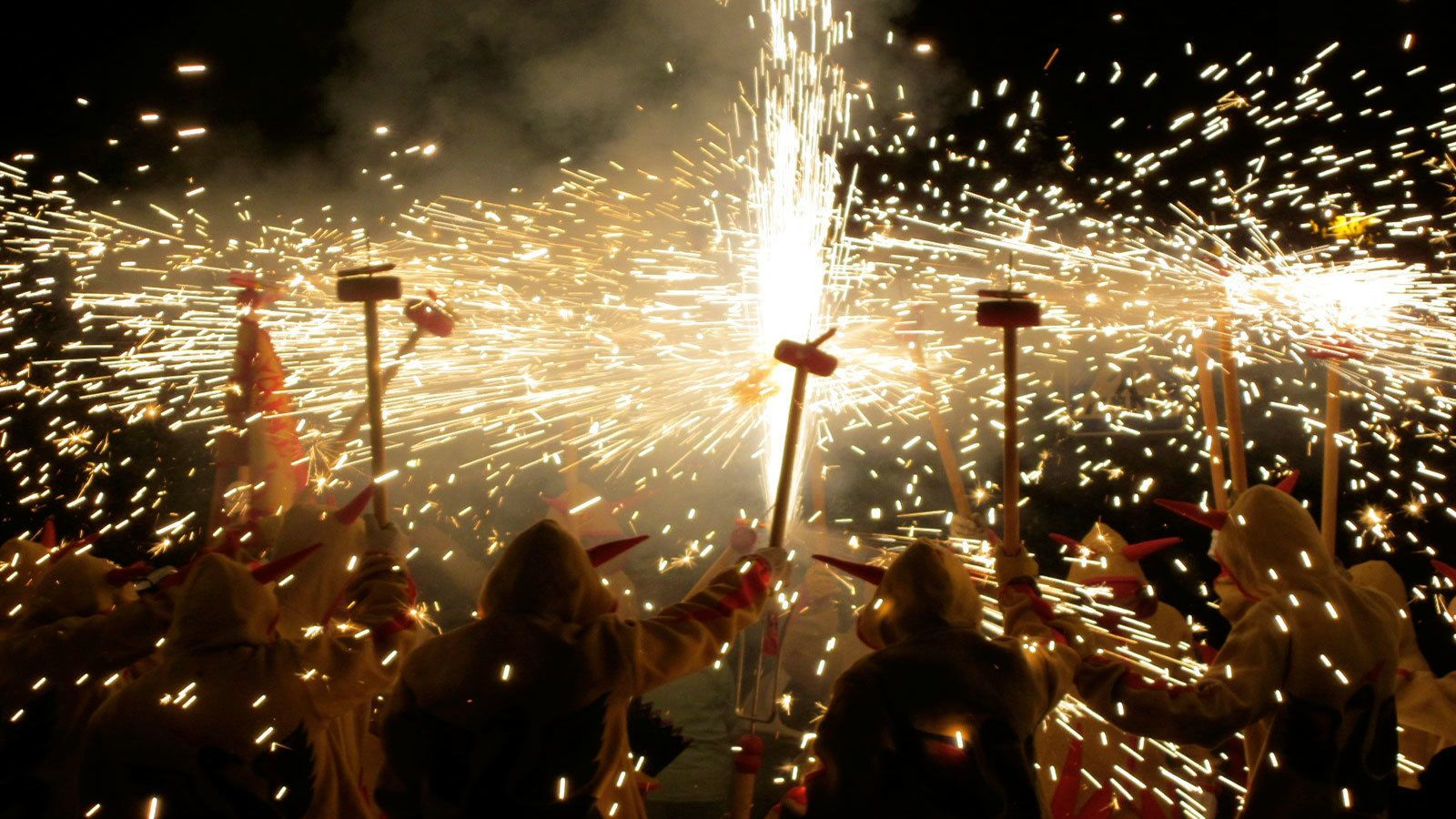 many people celebrating correfoc fire running in Barcelona