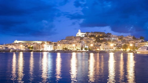 Ibiza at night with lights reflecting on the water.