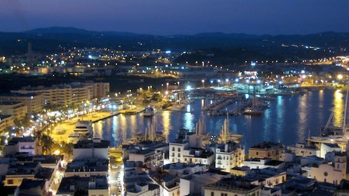 View of city and marina lit up at night in Ibiza.