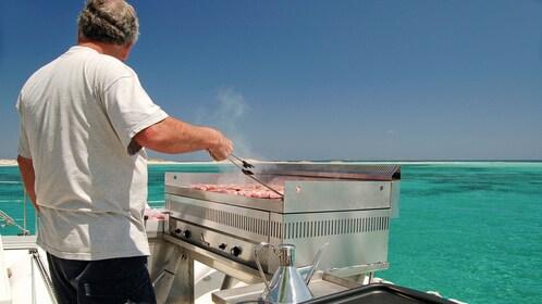 Man barbecuing on a catamaran in Ibiza.