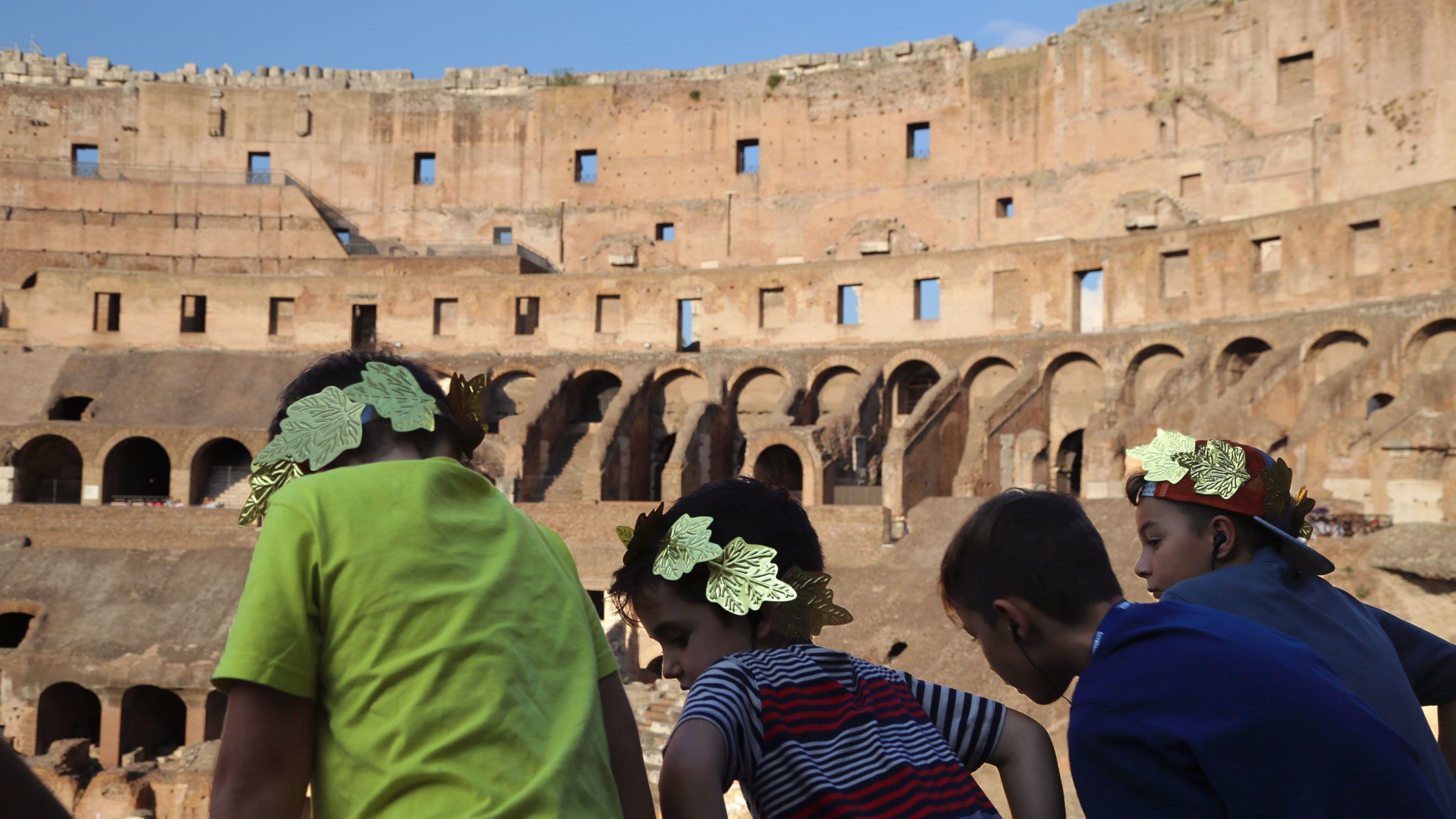 The Colosseum with a group of young boys wearing laurel wreaths in Rome.