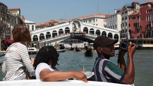 Boating tourists take a picture near the Rialto Bridge in Venice