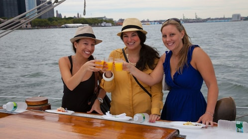 Trio of women toasting with mimosas aboard the Shearwater Sailing ship