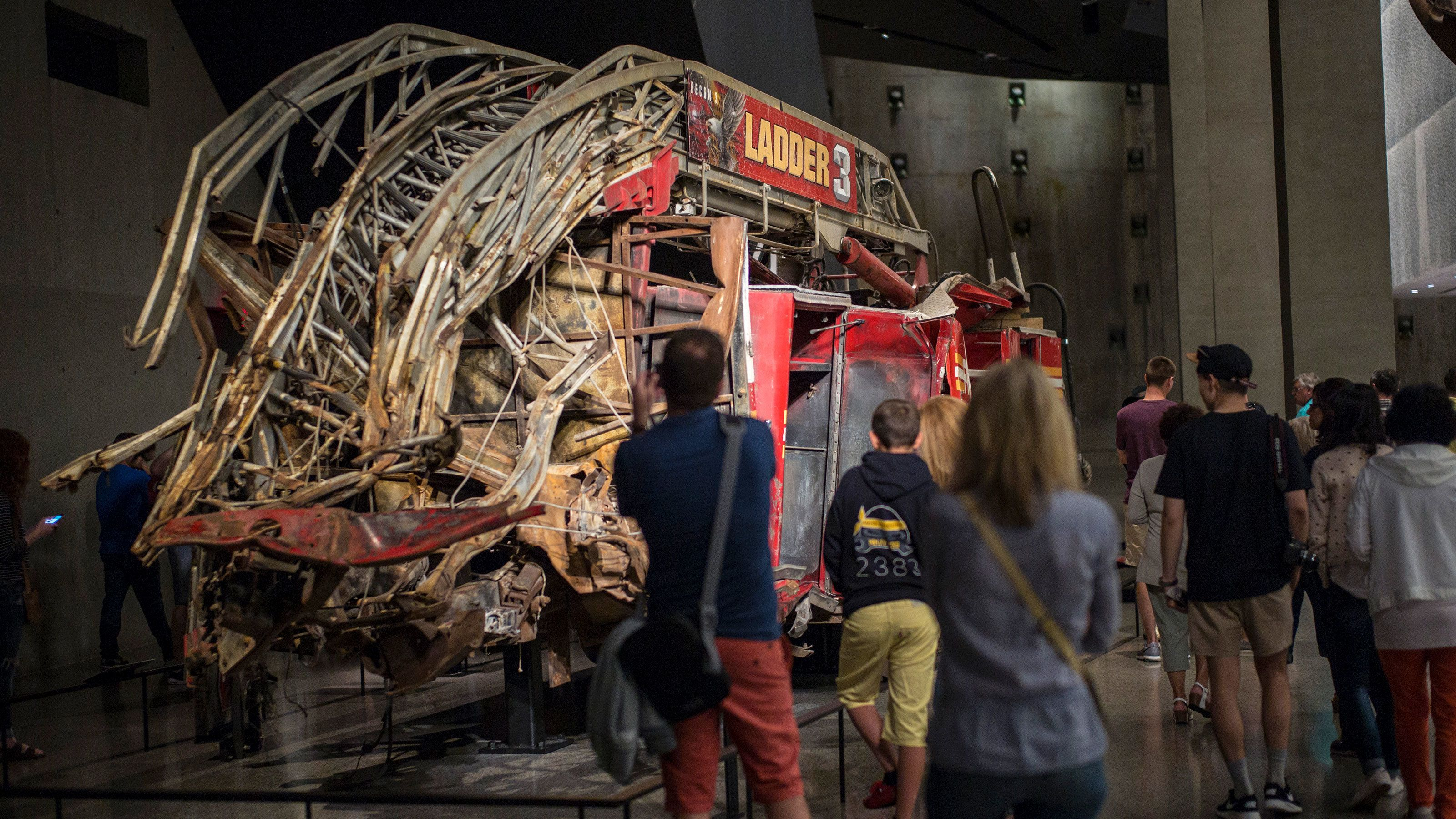 People looking at the remains of fire engine at the National September 11 Memorial Museum in New York