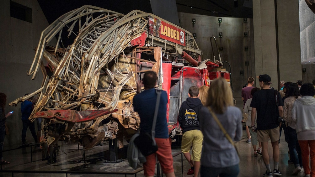 Show item 3 of 10. People looking at the remains of fire engine at the National September 11 Memorial Museum in New York