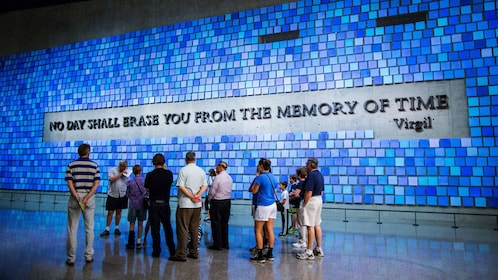People standing near quote mural on wall at the National September 11 Memorial Museum in New York