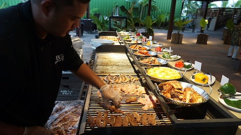 Chef placing meat on the grill