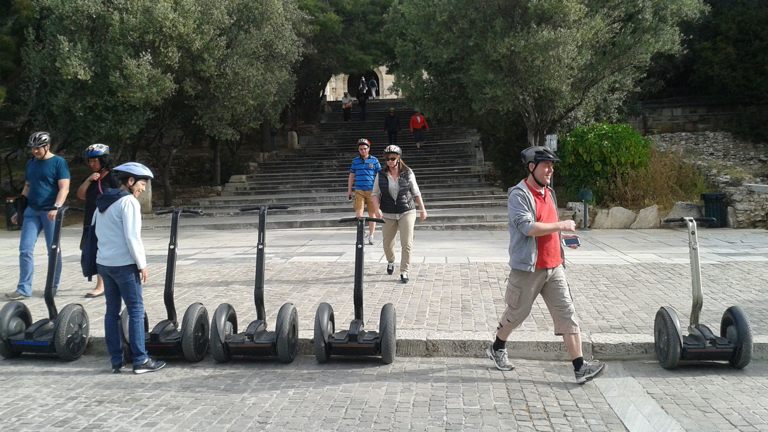 people in safety helmets about to ride their segways around Dionysou Aeropagitou in Athens