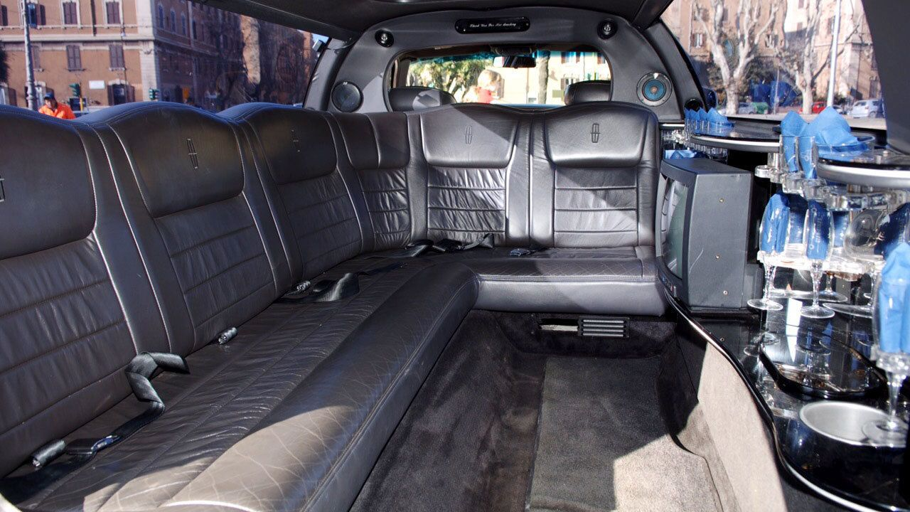 Interior of a limousine featuring black leather seats and wet bar