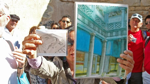 Tour guide showing illustrations of what the ruins originally looked like on Delos