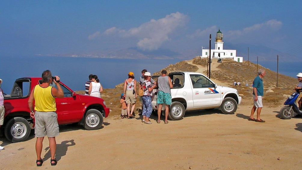 Tour group at a lookout near a lighthouse on Mykonos
