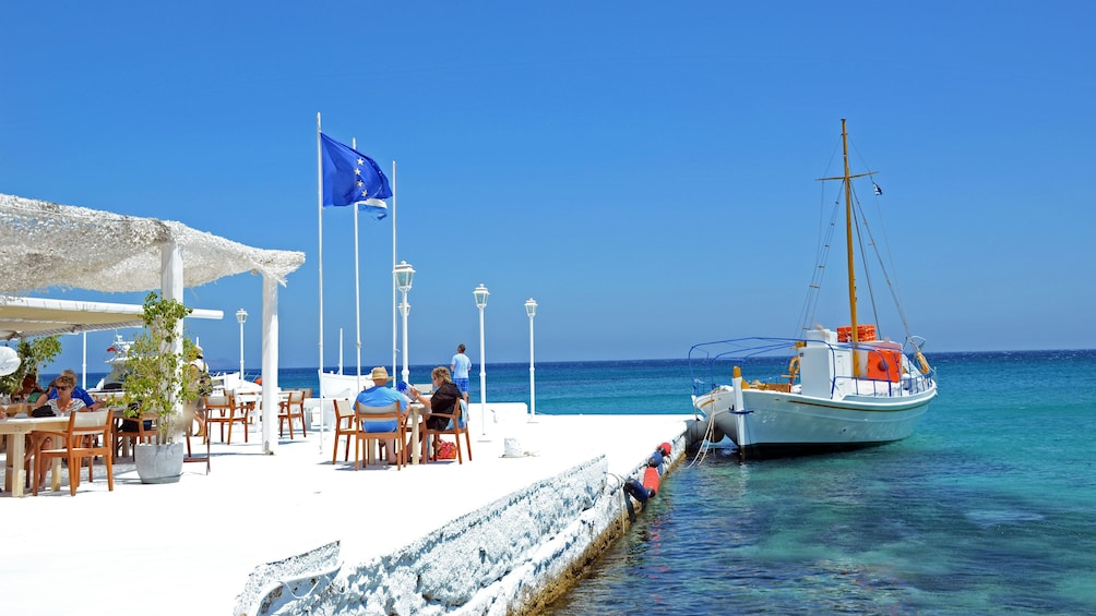 Couple eating lunch at a seaside restaurant with sailboat docked nearby on Mykonos