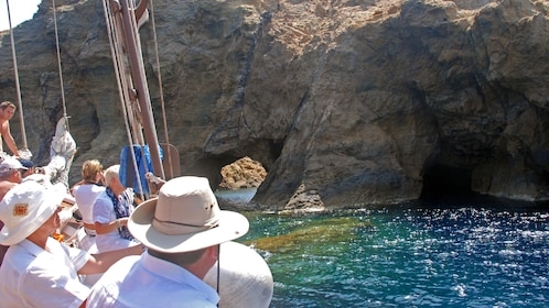 Sailboating tour group looking at caves and rock formations on the coast of Dragonissi