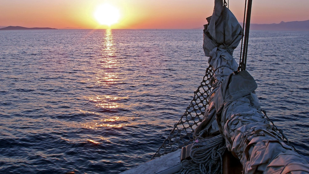 View of the sunsetting over the water from a sailboat in Mykonos