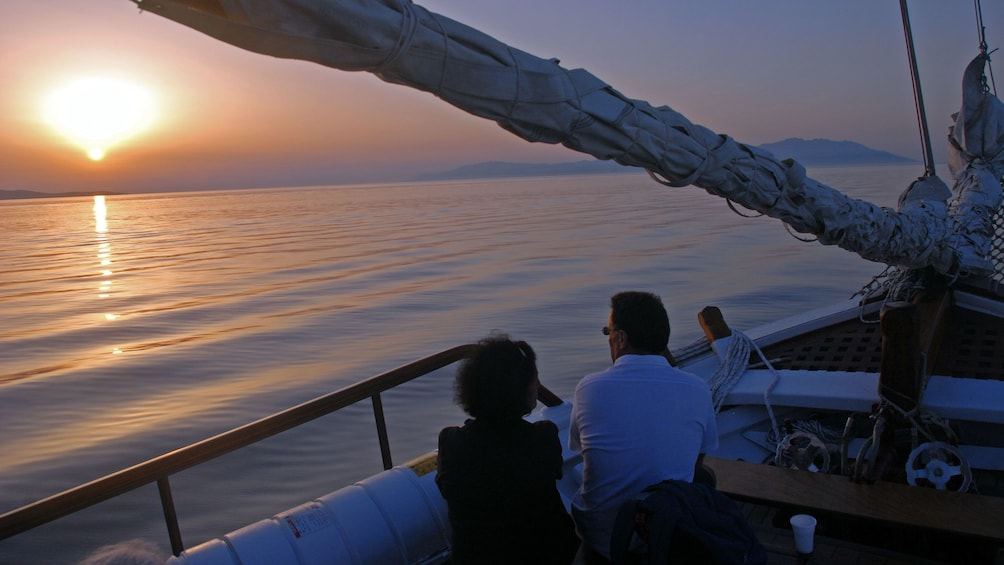 Couple watching the sunset from the deck of a sailboat in Mykonos