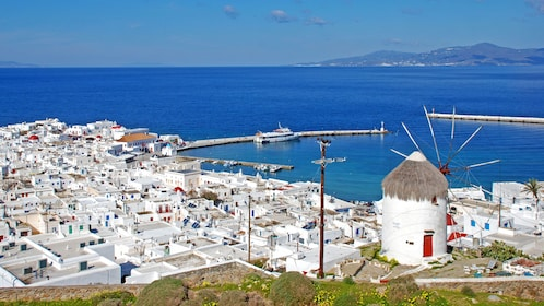 Windmill on a hill with the city below in Mykonos
