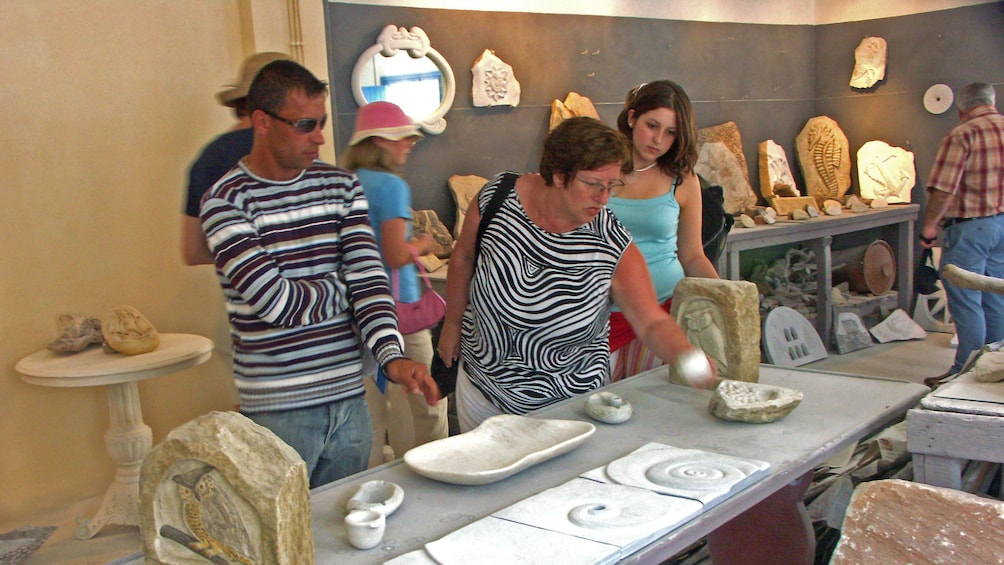 Group looking at handcrafted stone carvings in Tinos