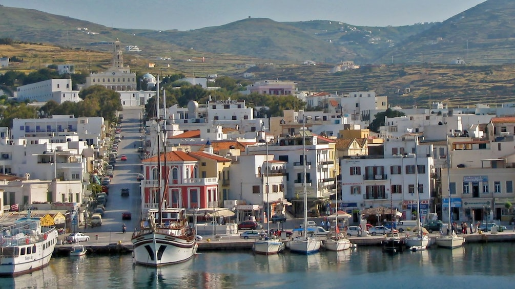 City with boats docked along the coast in Tinos