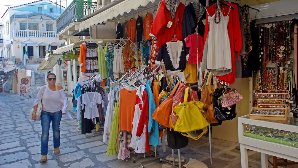 Woman shopping for clothes and jewelry at an open-air market in Tinos