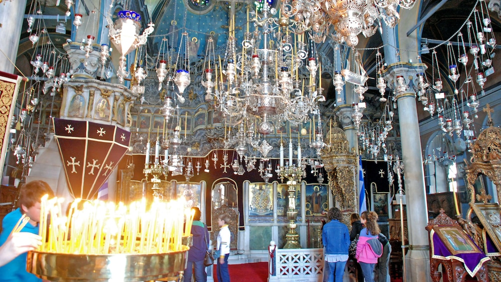 Chandeliers and incense burners hang from the ceiling at a church in Tinos