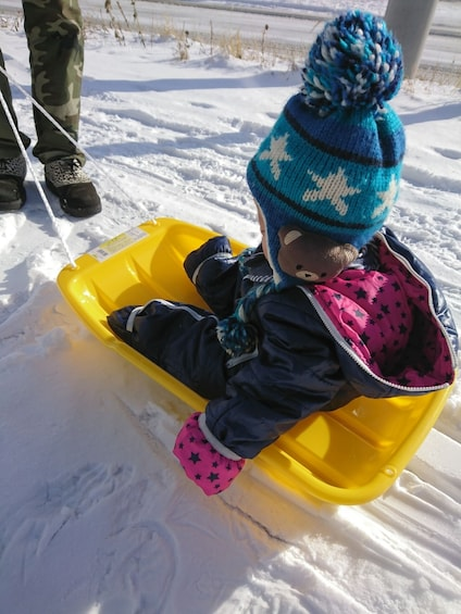 Show item 2 of 5. Small child sits in sled at Yeti Snow Park